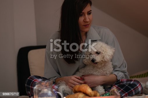 618750646istockphoto Woman lying on bed with dog 936670712