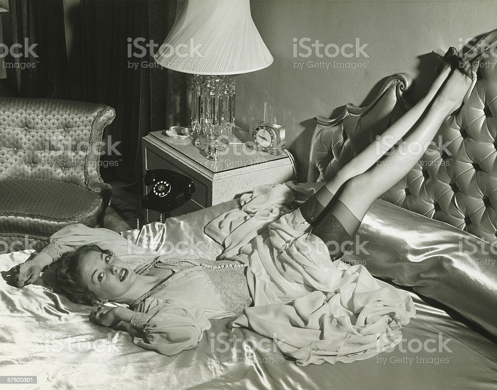 Woman lying on bed with legs on backrest, (B&W), elevated view stock photo