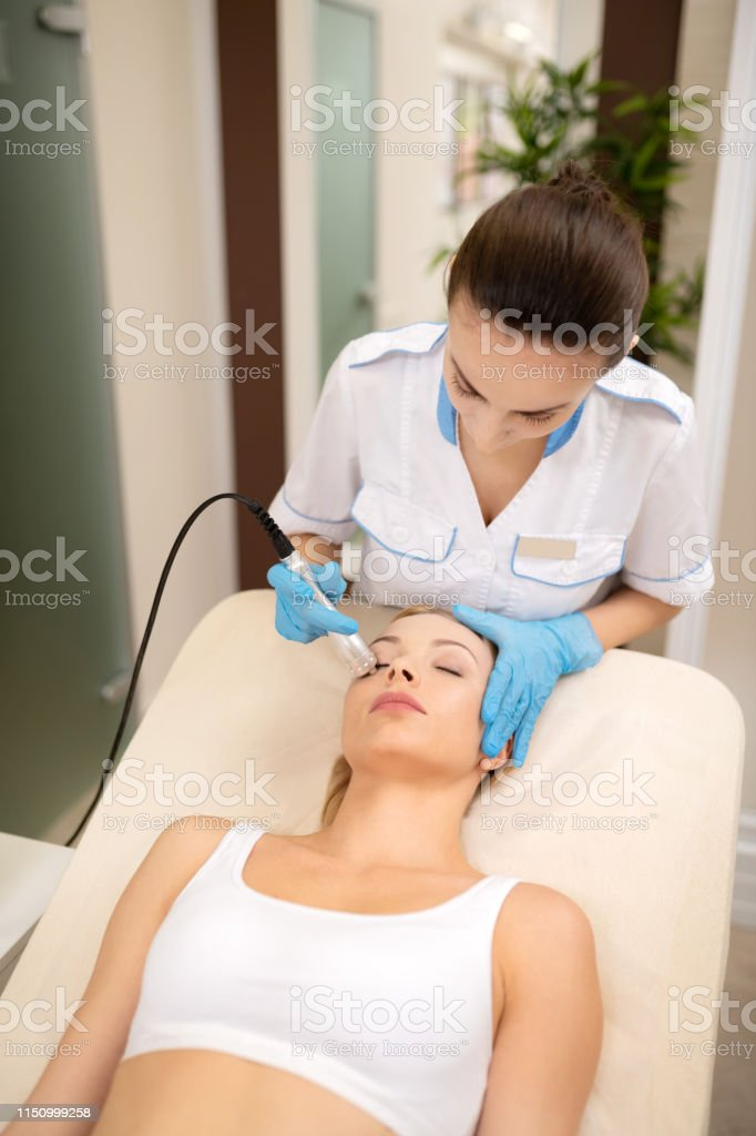 Beauty procedures. Woman wearing white top lying on coach and having...