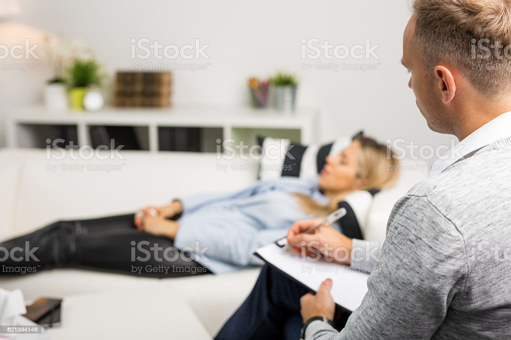 Woman lying on couch at doctors office stock photo