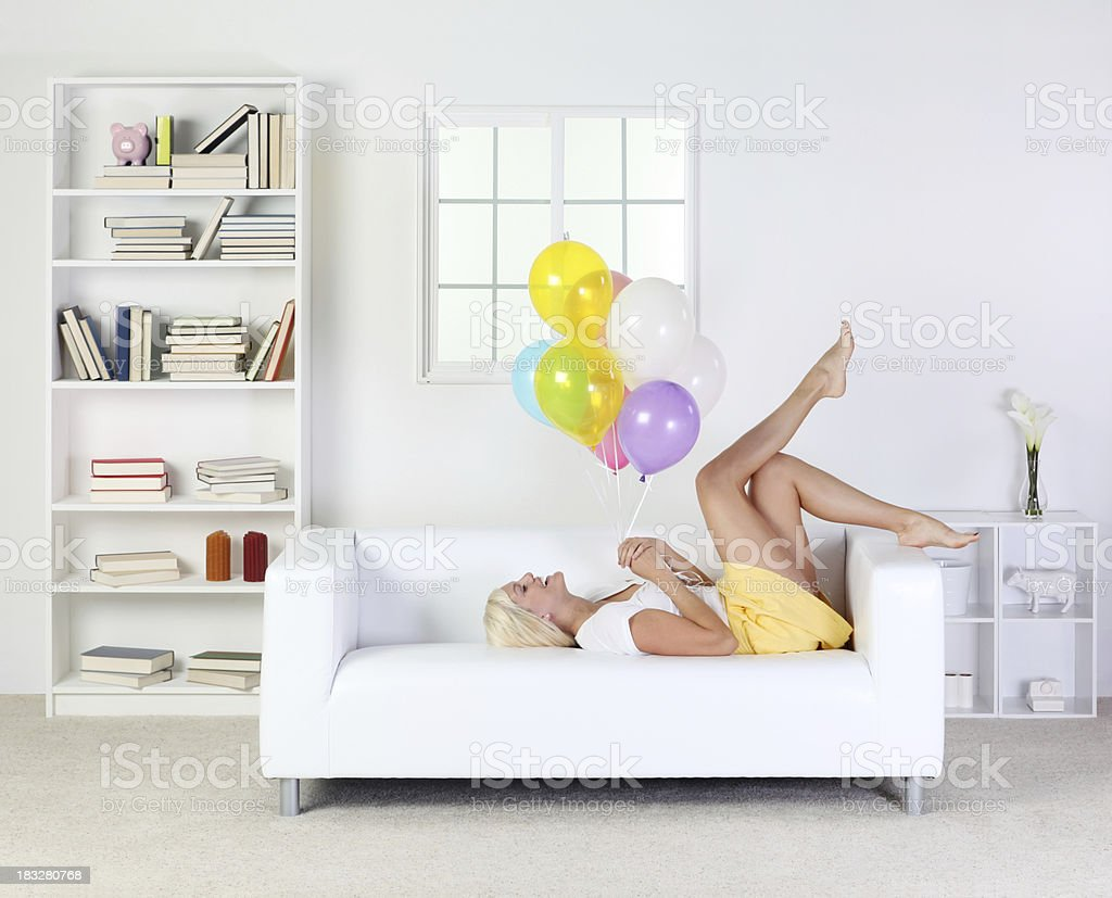 Woman lying on couch with a bunch of balloons royalty-free stock photo