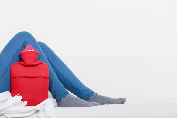 Woman lying on couch with hot water bottle Warming up during cold winter or autumn days. Woman lying on couch with hot water bottle, legs shot only. hot water bottle stock pictures, royalty-free photos & images