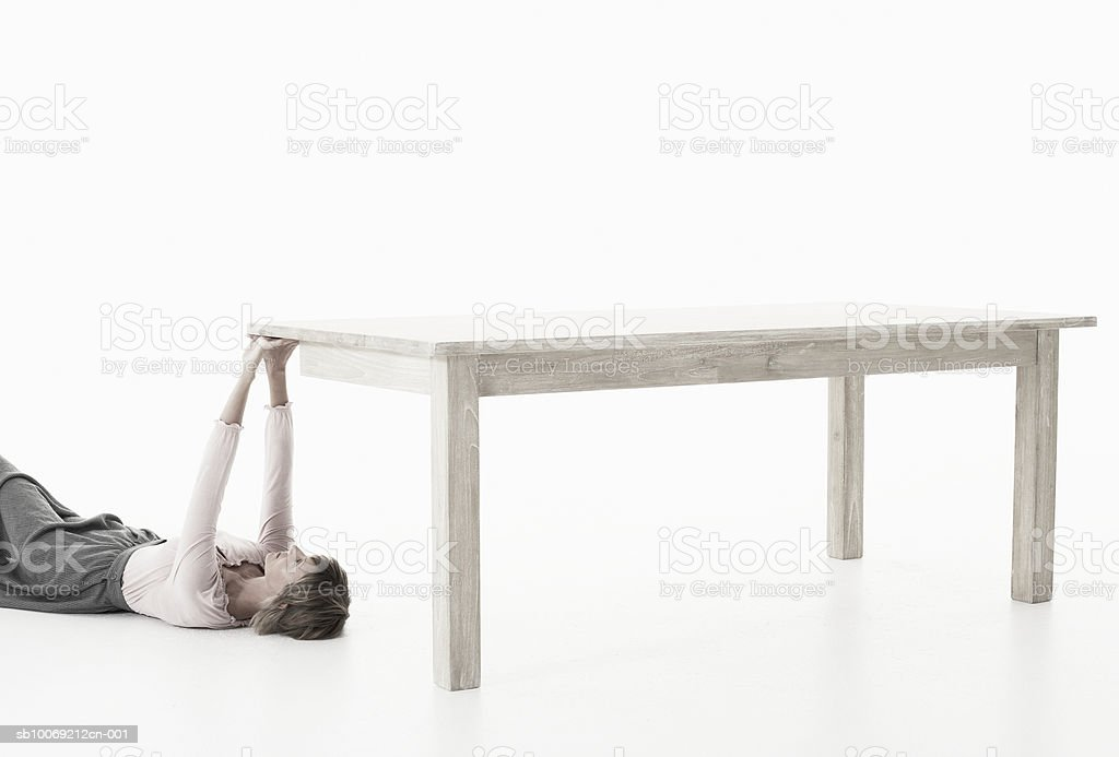 Woman lying on floor supporting one corner of table against white background royalty-free stock photo