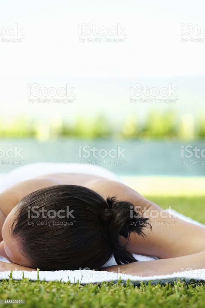 Woman lying on grass at a park - copyspace royalty-free stock photo