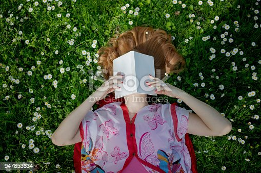 Woman's holding a book in front of her face, lying on grass