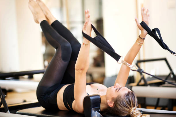 woman lying on her back atop exercise bench - metodo pilates foto e immagini stock