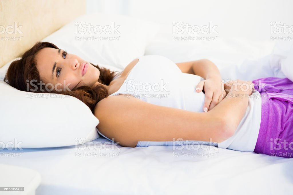 Woman lying on her bed with a belly pain stock photo