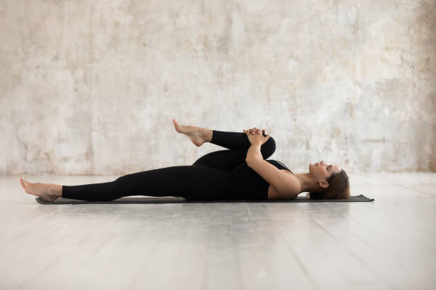 Woman lying on mat doing Half Knees to Chest Pose Woman wear black sport clothes lying on floor practising asana do Half Knees to Chest Pose near grunge wall beige textured background, help ease back pain, flexible body stretch for beginners concept apanasana stock pictures, royalty-free photos & images