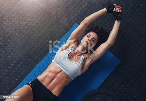 istock Woman lying on mat doing stretching exercise 538675162
