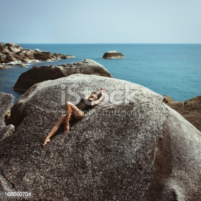 Woman in black swimsuit lying on rock in front of the sea.