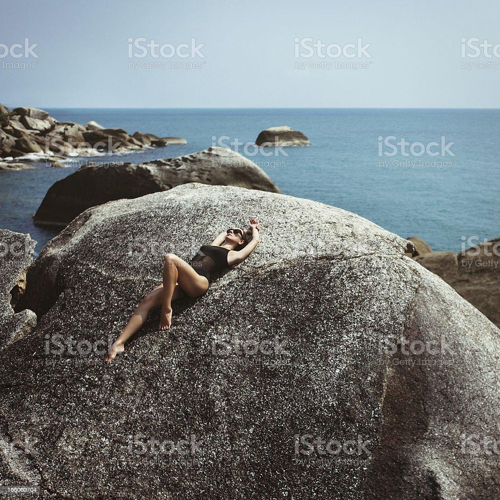 Woman lying on rock stock photo