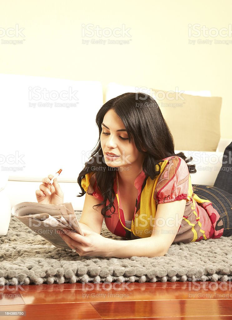 Woman lying on rug, reviewing contents of the newspaper royalty-free stock photo