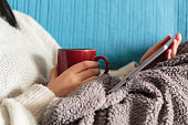 Woman lying on sofa with blanket watching a movie on tablet and holding a mug