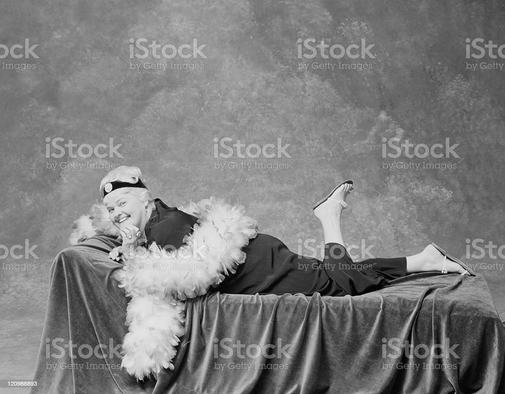 Woman lying on sofa with feather boa, smiling, portrait royalty-free stock photo