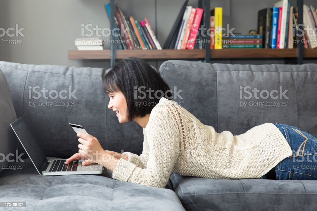 Woman lying on stomach on couch on laptop with credit card stock photo