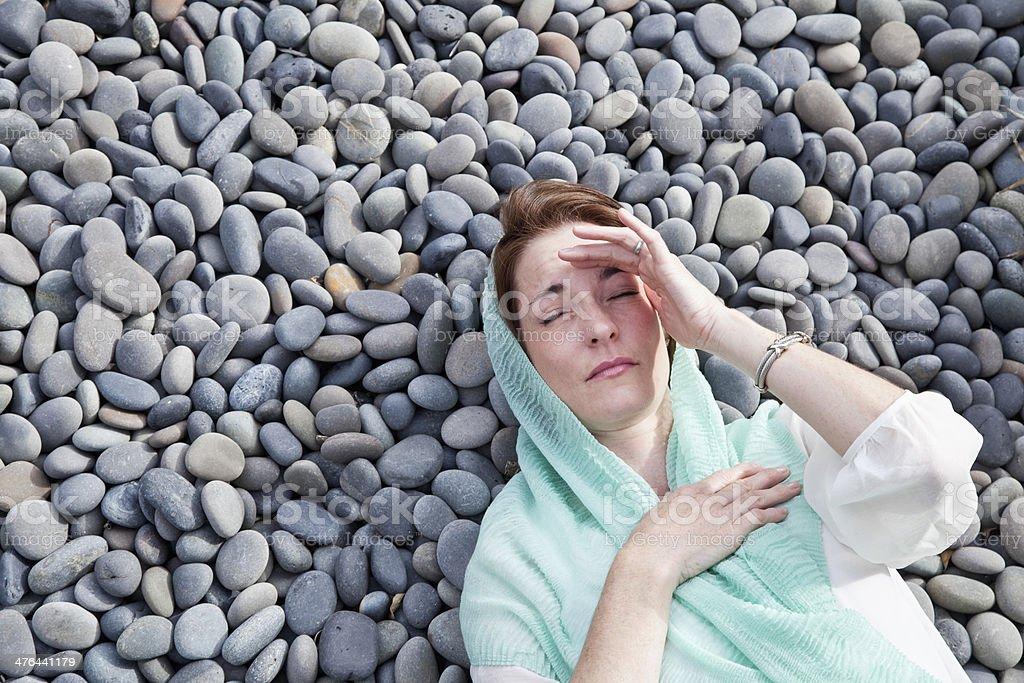 Woman lying on stones royalty-free stock photo