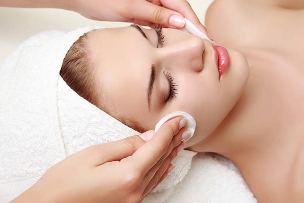Woman lying on table receiving facial treatment stock photo
