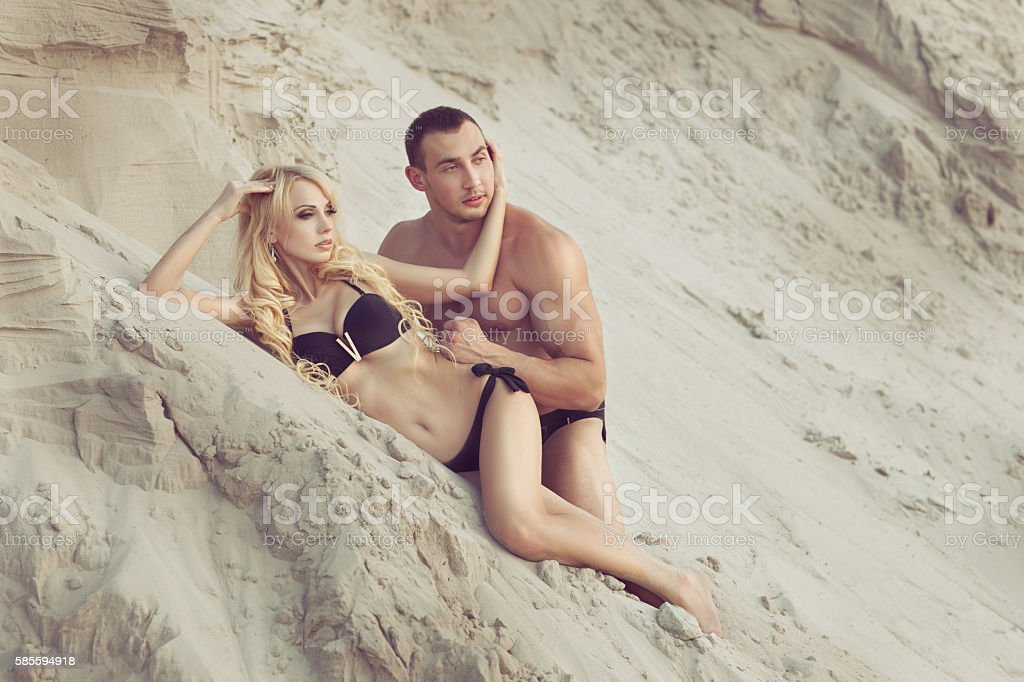 Woman lying on the beach with a man. stock photo
