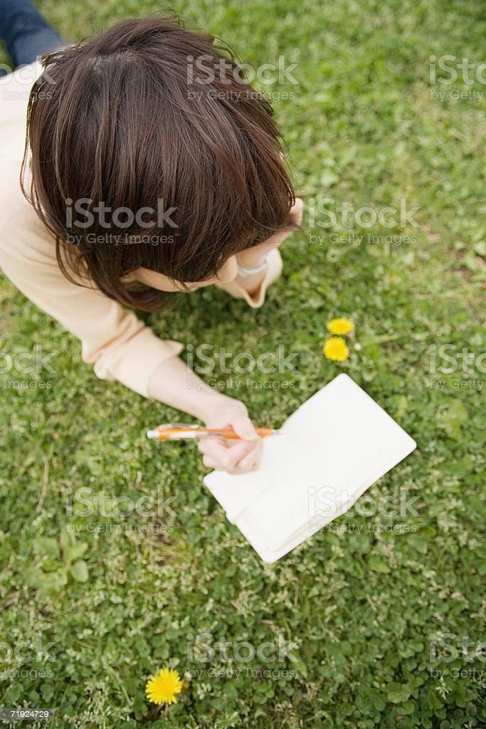 Woman lying on the grass and writing royalty-free stock photo