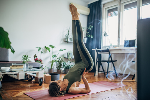 One beautiful young woman doing yoga on exercise mat in her living room, lying on upper back and holding her lower back in balance.