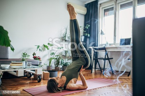 istock Woman lying on upper back and holding her lower back in balance 1243198580