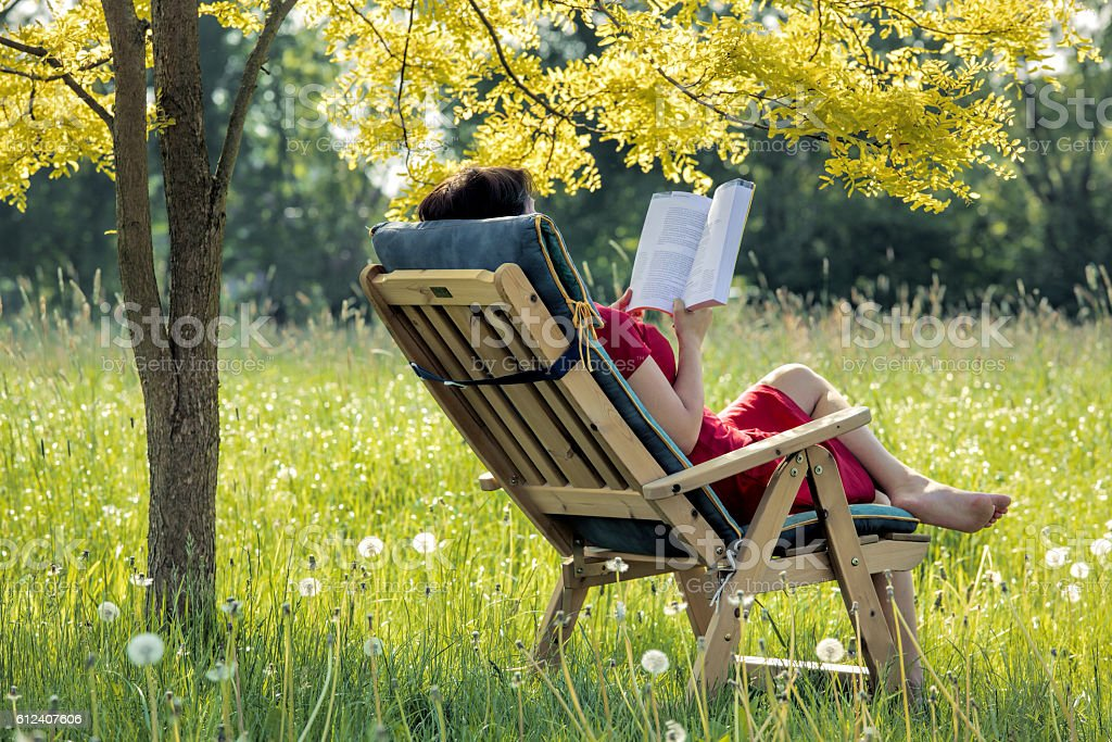 Woman lying outdoors in deck chair reading book stock photo