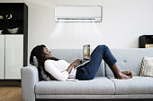 istock Woman Lying Under Air Conditioner On Couch Using Laptop 1325532617