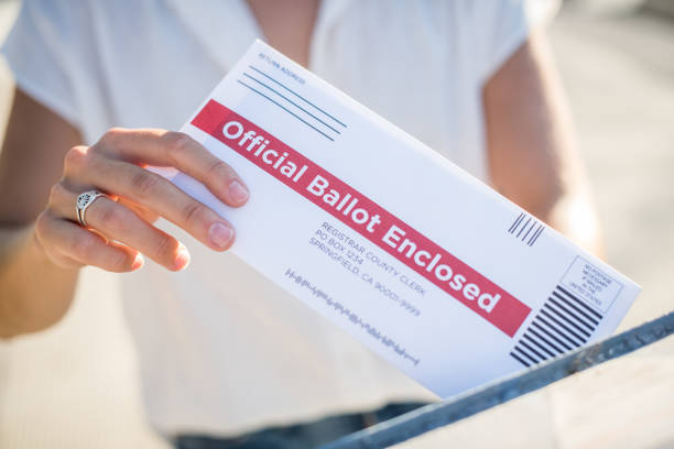 woman mailing her absentee voter ballot - ballot stock pictures, royalty-free photos & images