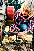 Woman reattaching a blade after cleaning the dirt from it on a garden rotovator.