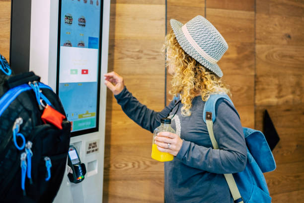 Woman make food order in modern display at fast food restaurant - self-service panel technology and people in travel lifestyle taking hamburger to eat stock photo
