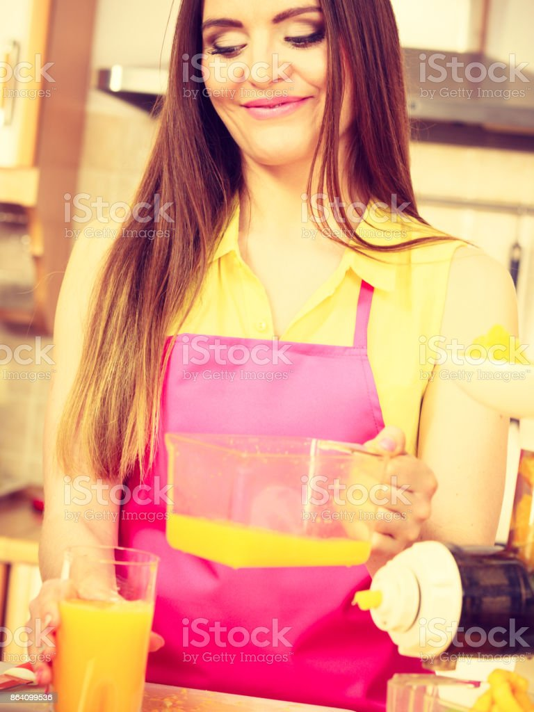 Woman make orange juice in juicer machine pouring drink in glass royalty-free stock photo