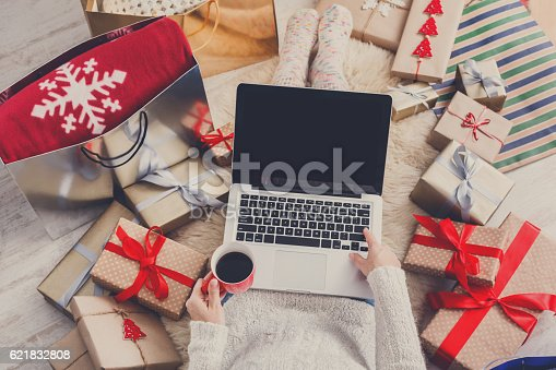 istock Woman makes christmas shopping online with laptop, above view 621832808
