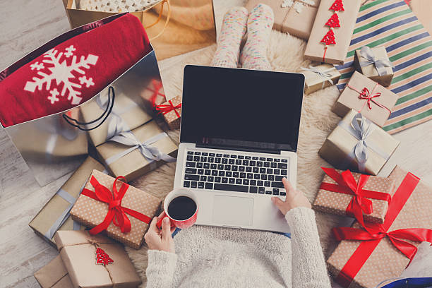 Woman makes christmas shopping online with laptop, above view stock photo