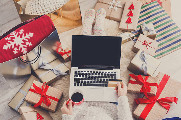 woman makes christmas shopping online with laptop, above view - shopping stock photos and pictures