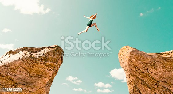 istock Woman makes dangerous jump between two rock formations 1218610050