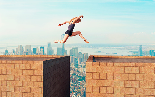 istock Woman makes dangerous jump over gap between two tall buildings 885968086