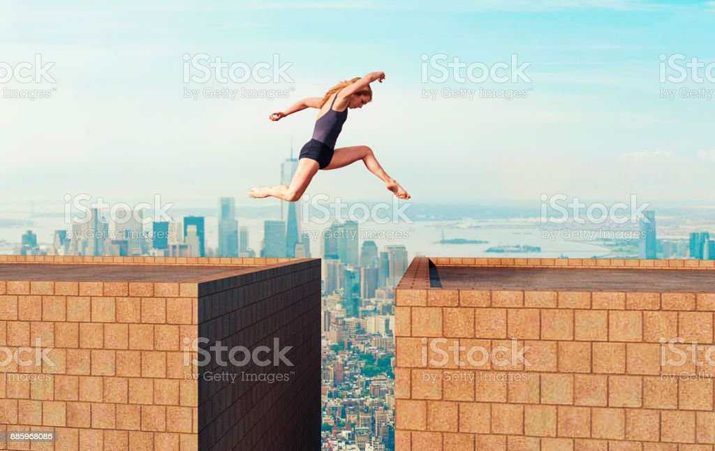 Woman makes dangerous jump over gap between two tall buildings stock photo