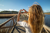Woman makes a heart shape finger frame, she stands on a wooden bridge above lake, wheat meadow on background.