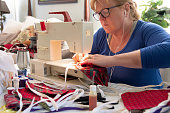 A woman at home makes handmade masks in preparation for coronavirus pandemic.