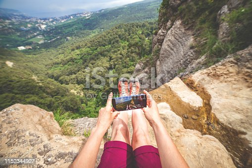Woman makes photo of her boots and landscape background sitting at the edge of a rock near stream. View on behalf of photographer.