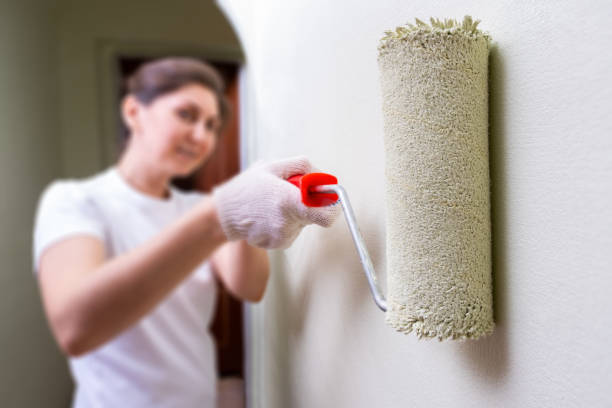 woman makes repairs in the apartment stock photo