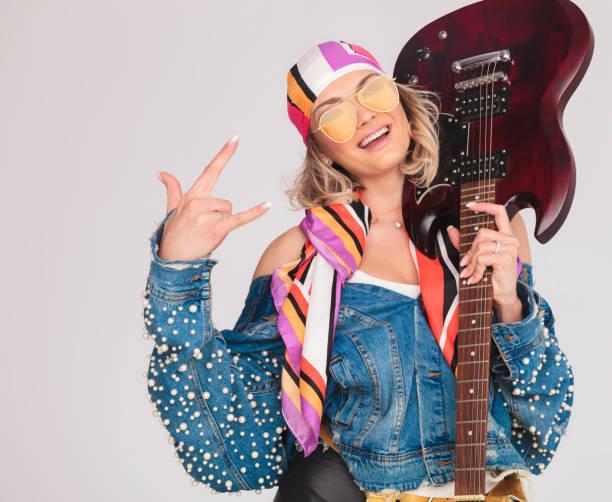 frau macht rock auf schild haltend gitarre auf schulter - schal mit sternen stock-fotos und bilder