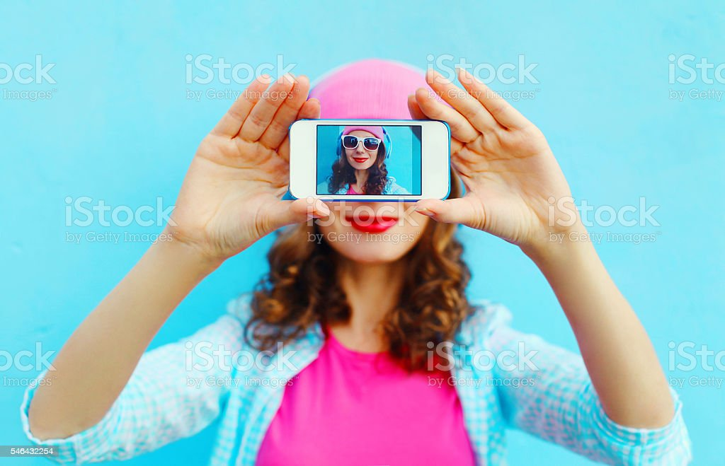 Woman makes self-portrait on smartphone view screen over colorfu stock photo