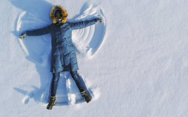 frau lässt schneelangel im schnee liegen top view. luftbild. - damen hosen angels stock-fotos und bilder