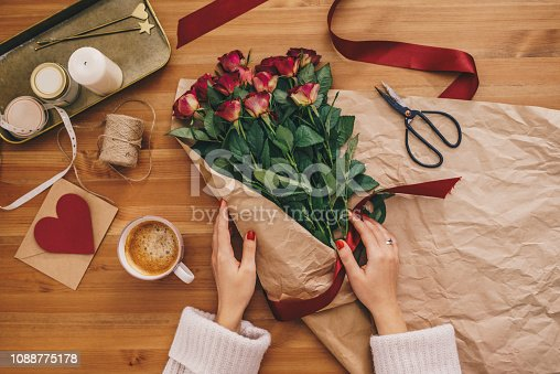 Top view of woman's hands creating a bouquet of rose flowers on a wooden table