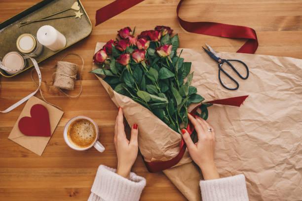 Frau macht einen Strauß roter Rosen – Foto