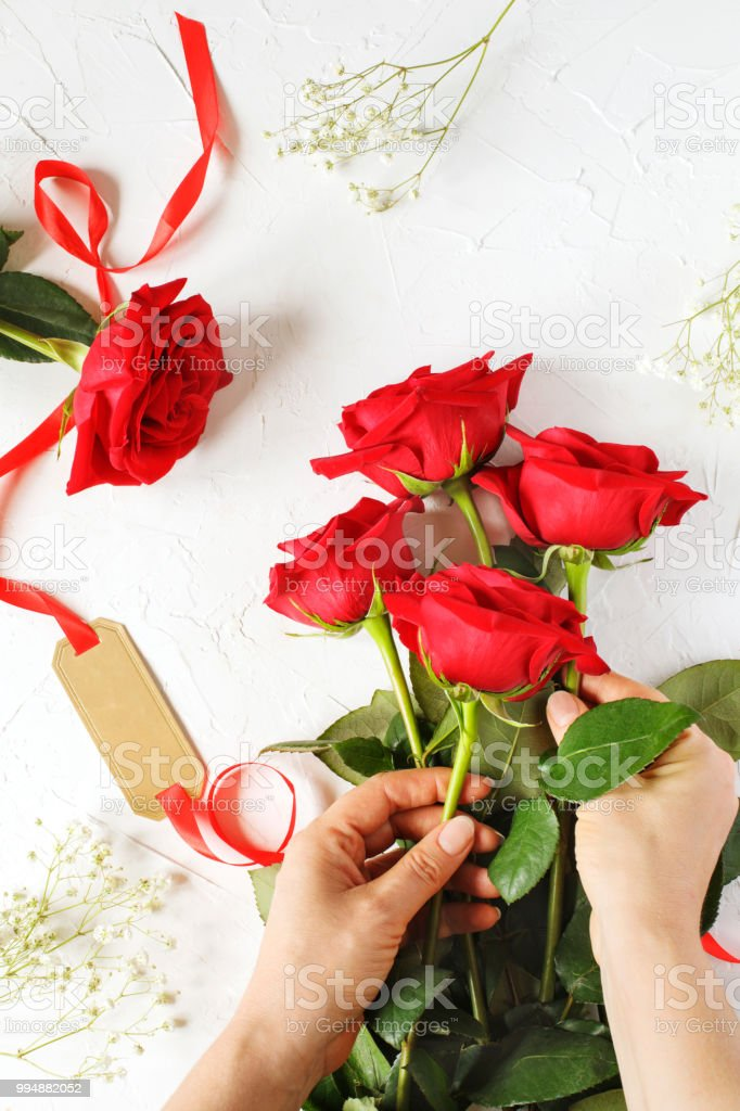 Woman making a bouquet of red roses, top view.