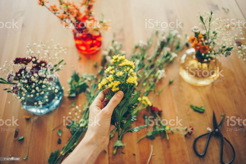 Top view of woman\'s hands creating a bouquet of spring flowers on a...