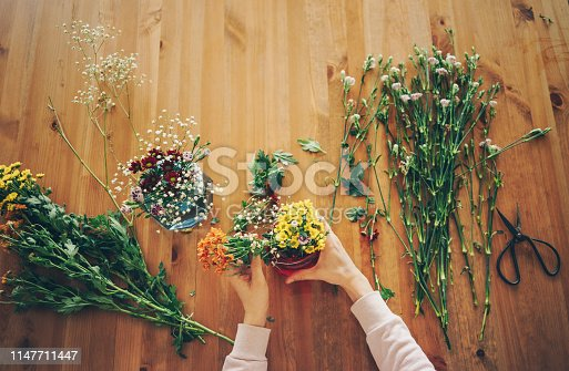 Top view of woman's hands creating a bouquet of spring flowers on a wooden table