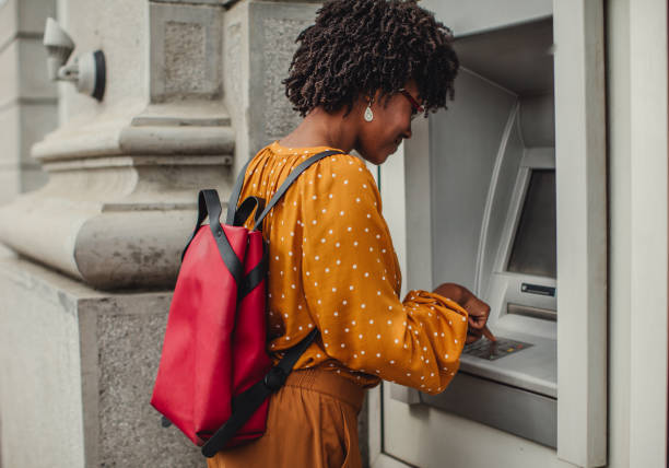 Woman Making A Cash Withdrawal At An ATM woman making a cash withdrawal at an ATM banks and atms stock pictures, royalty-free photos & images